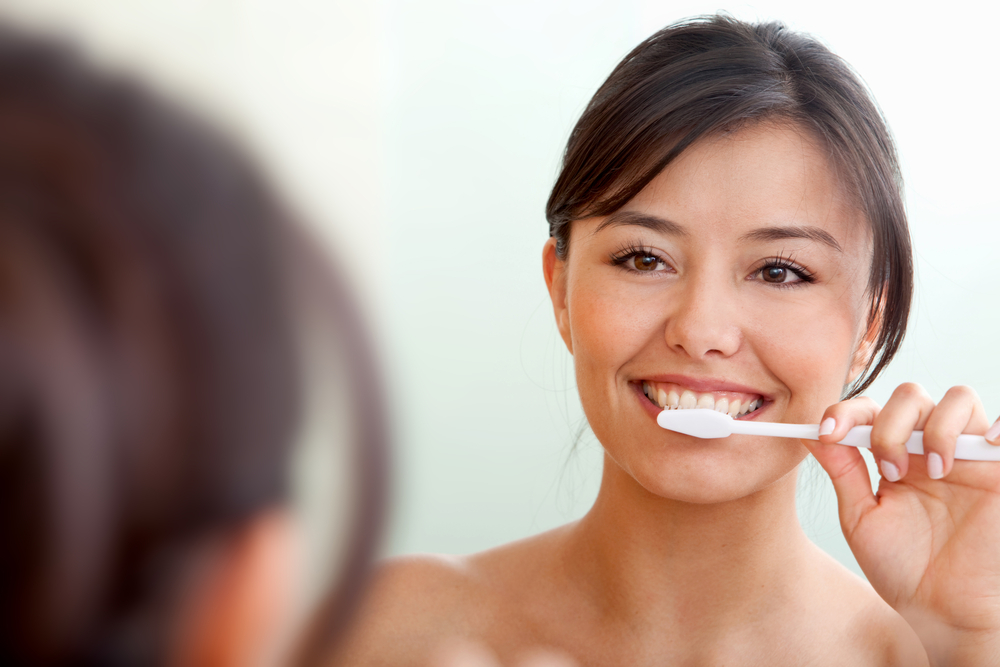 Woman in front of a mirror brushing her teeth-1