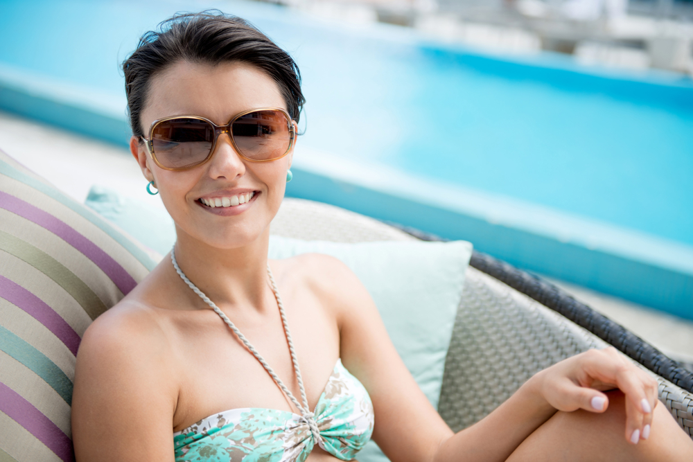 Woman by the swimming pool enjoying her vacations