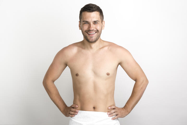 happy-shirtless-man-posing-against-white-wall